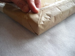 Fold the material up against the second side and fold onto the bottom of the seat as shown